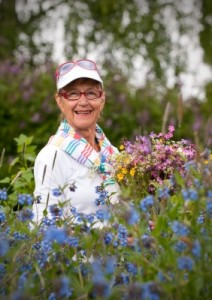 smiling elderly lady gardener with flowers